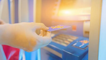 Hand die ATM-kaart in de bankautomaat stopt om zich terug te trekken, mensen staan ??in de rij om geld te ontvangen. Uitstekende kleur