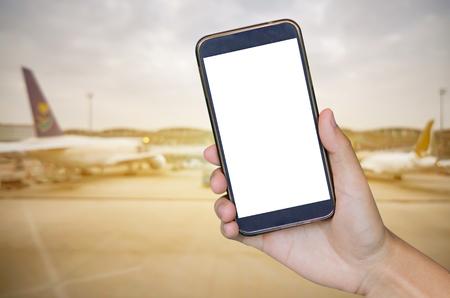 공항에서 승객의 흐린 배경 위에 모바일 스마트 폰, 태블릿, 핸드폰을 들고 남자 손, 사람들은 복고풍 필터 효과와 함께 공항에서 걷고