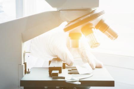 Medizinisches Labor, Doktor oder Wissenschaftler Hände mit Mikroskop für Chemie Test Proben, Prüfung, Wissenschaftliche und Gesundheitswesen Forschung Labor Hintergrund.vintage Farbe