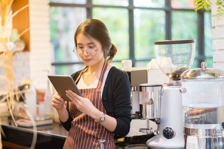 Beautiful young baristas using a digital tablet smiling and looking at her touchscreen smartphone get orders from and order raw materials online shopping while standing aat coffee bar  cafe counter