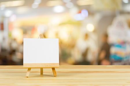 Ezel met blanco canvas op houten tafel, billboard op houten bureau met meegeleverde bokeh achtergrond, sjabloon mock voor montage van uw product.vintage kleur weergeven Stockfoto