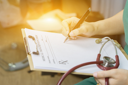 female doctor writing a prescription with stethoscope on hospital holding clipboard,Medical Exam,Healthcare and medical concept,test results,vintage color,selective focus
