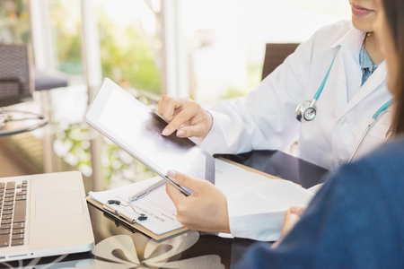 Female Doctor consulting  and discussing records with female patient, presenting results on tablet computer, sitting at desk., selective focus, vintage color