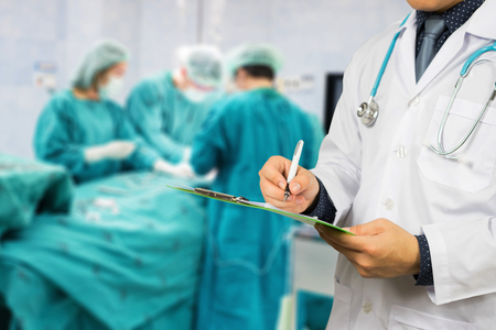 Male Doctor with files and stethoscope on hospital corridor holding clipboard and writing a prescription,Doctors Medical Exam,Healthcare and medical concept,test results, registration,selective focus.