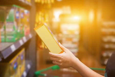In the hands of a handful of supermarkets.Woman hand grabs box in supermarket, retail and people concept , selective focus ,vintage color,copy space