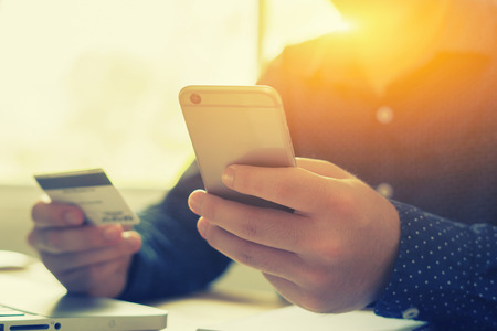 man verifies credit card account balance on smartphone with mobile banking application.Online payment Technology Shopping,selective focus,vintage color