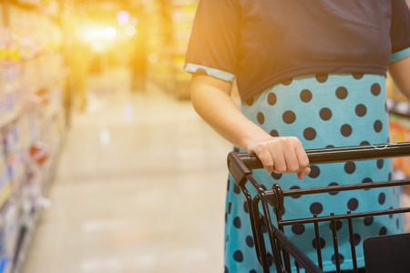 Female Hand Close Up With Shopping Cart in a Supermarket Walking Trough the Aisle,trolley in department store bokeh background,vintage color,copy space,selective focus Stock Photo