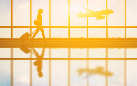 travel concept, people in the airports ,Silhouette of young girl with luggage walking at airport, women showing something through the window,selective focus,vintage tone color Banco de Imagens