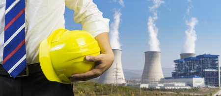 engineering management construction ,engineer or worker hold in hand yellow helmet for workers security  on working  site Coal power plant background.  business Man ,selective focus,vintage tone Stock Photo