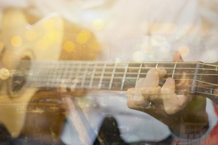 Double exposure of Men playing acoustic guitar on night light Bokehof city scape abstract background,selective focus,vintage color Imagens