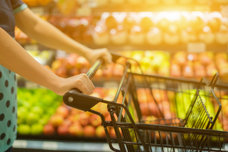 Vrouwelijke hand close-up met winkelwagen in een supermarkt wandelen via de gangpad, trolley in warenhuis bokeh achtergrond, vintage kleur, kopie ruimte, selectieve focus