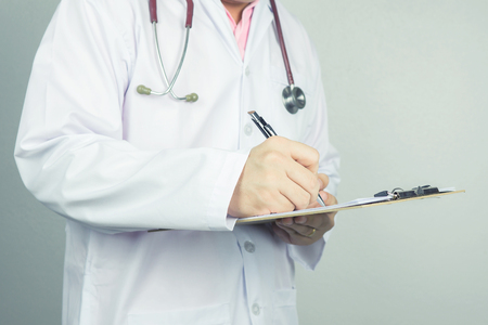 male doctor writing a prescription with stethoscope on hospital holding clipboard,Medical Exam,Healthcare and medical concept,test results,vintage color,selective focus