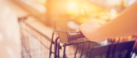 Female Hand Close Up With Shopping Cart in a Supermarket Walking Trough the Aisle,trolley in department store bokeh background,vintage color,copy space