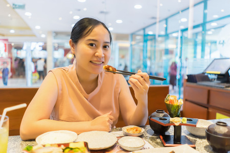 beautiful asian lady in restaurant , she eating delicious sushi on sticks and smiling widely, a healthy Japanese food,Diet, dieting wellness concept,vintage color Imagens - 80699500