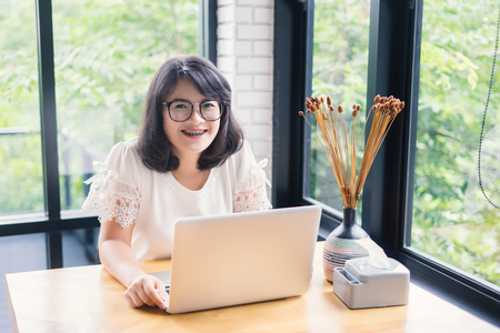 Beautiful young smiling woman working on laptop and drinking coffee at home or co-working space,businesswoman in glasses looking at the camera. Attractive female manager after hard working day,vintage