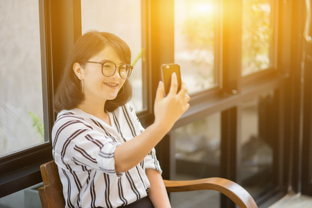 Happy young Asian woman smiling and taking selfie with smartphone in coffee shop cafeteria,vintage color Imagens