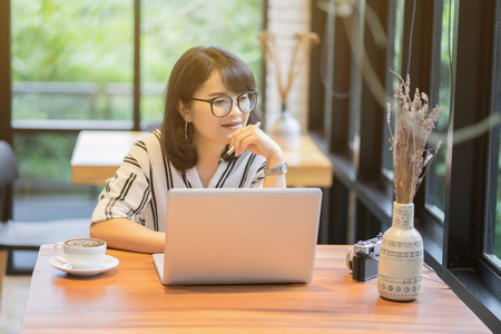 Asian businesswoman smiling and thinking in front of laptop while sitting at co-working space office to manage her coffee shop.Small business pondering over ideas for new business project,vintage tone