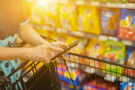 girl leaning on shopping cart, using a mobile phone and smiling, trolley in department store bokeh background,vintage color,copy space,consumerism, retail technology and people concept