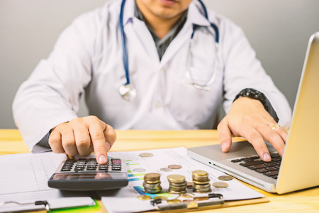 young medical doctor caucasian healthcare professional wearing a white coat with stethoscope in hospital ,calculates on an electronic calculator,medical fee concept,selective focus,vintage color