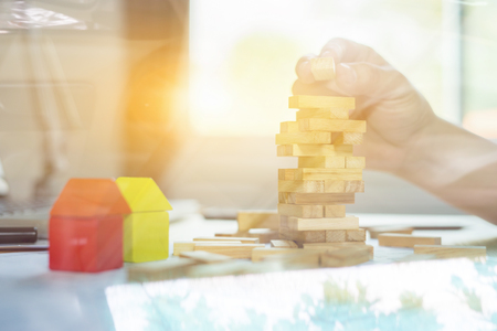 Planning, risk and strategy of project management in business, businessman and engineer  playing a blocks wood game on blueprint or architectural project on a tower,construction vintage tone.