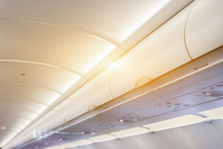 Overhead compartment - detail shot of an airplane cabin interior,selective focus ,vintage color