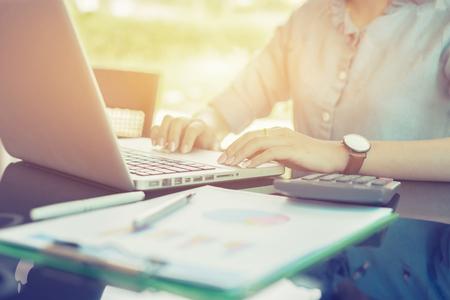 ビジネス女性金融検査官・事務局長の報告、計算や残高を確認します。内国歳入庁は、ノート パソコンと電卓でチェック ドキュメントを検査します 写真素材