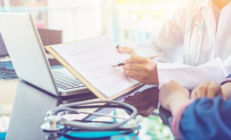 Les mains du médecin pointant sur un tableau électro-cardiogramme sur le pavé du presse-papiers remplissent les antécédents médicaux avec un stylo. Aide d'un cardiologue, un médecin rend le physique cardiaque, un document de mesure du pouls, une idée de l'arythmie