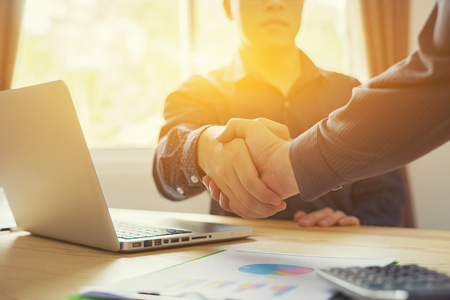 Great job,Sealing a deal,Successful business,Handshake,Businessman join together,Good agreement.two business people shaking hands standing at the working place,selective focus,Vintage color
