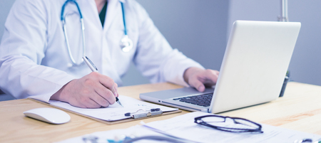 Doctor working in hospital writing a prescription, Healthcare and medical concept,test results in background,Stethoscope with clipboard and Laptop on desk,vintage color,selective focus
