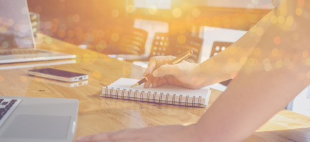 Male manager putting his ideas and writing business plan at workplace,man holding pens and papers, making notes in documents, on the table in office,vintage color,morning light ,selective focus. Imagens
