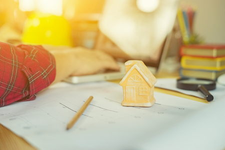 huis model met architect man aan het werk met laptop en blauwdrukken, ingenieur inspectie op de werkplek voor architectonische plan, schetsen een bouwproject, selectieve aandacht, Business concept vintage kleur
