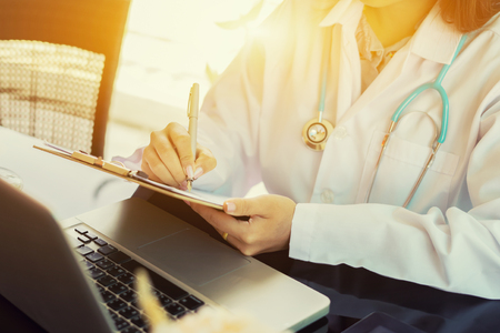 female doctor,surgeon,nurse,pharmacy with stethoscope on hospital holding clipboard,writing a prescription,Medical Exam,Healthcare and medical concept,test results,vintage color,selective focus