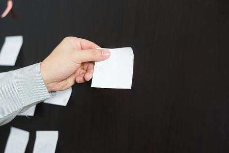 手のついた空黄色い紙、ブラック ボードに掲示、ポストイット、メモ、実業家の手ピン付箋、ヴィンテージ色