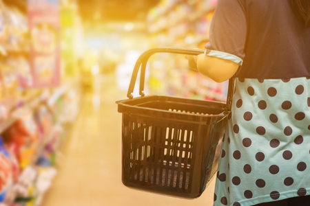 Female Hand holds a shopping basket in a Supermarket Walking Trough the Aisle, in department store bokeh background, business retails concept,vintage color,copy space Imagens