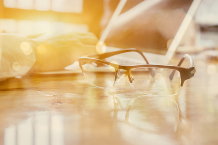Eye Glasses on Businessman Wooden Table with Other Stuffs - Keyboard, Notebook, Pen and Phone.Office workplace with laptop , smart phone ,businessman work in Office desk,selective focus ,vintage tone