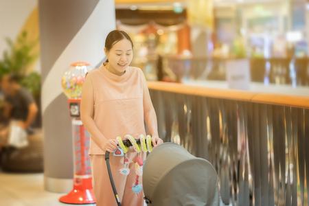 유모차 슈퍼마켓 및 쇼핑몰, 빈티지 색상 선택적 포커스를 추진하는 동안 산책하는 젊은 아시아 어머니