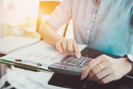 Vrouwelijke ondernemers boekhouder of financiële inspecteur handen maken rapport, berekenen of controleren saldo op rekenmachine. Huisfinanciën, investering, economie, besparingsgeld of verzekeringsconcept, uitstekende kleur