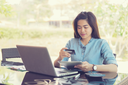 online shopping, woman smiling and looking in front of her as she uses her credit card with her laptop.shopping and retail concept,vintage color