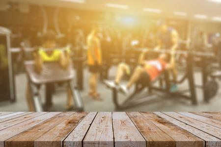 Leeg bruin houten lijstbovenkant op vage achtergrond van fitness gymnastiek, Jongerengroep vrouwen en mannen die sport, binnenland doen van nieuwe moderne club met materiaal