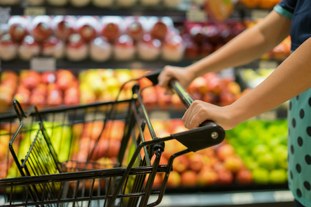 여성 손을 슈퍼마켓에서 쇼핑 카트를 닫습니다. 여유롭게 산책, 백화점 bokeh 배경, 빈티지 색상, 공간, 선택적 포커스에서 트롤리 통로