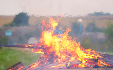 torrid: Large bonfire burning with large logs on the background of the beach