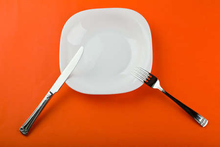 white plate with fork and knife on paper Stock Photo