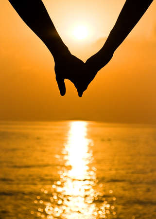 true love: Young couple holding hands at sunset Stock Photo