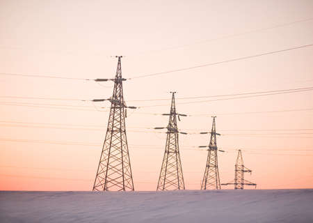 Electricity pylons and lines above a freeway  at sunrise Stock Photo - 13017162