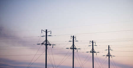 Electricity pylons and lines above a freeway  at sunrise Stock Photo