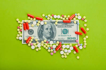 Pills and tablets on top of US paper currency