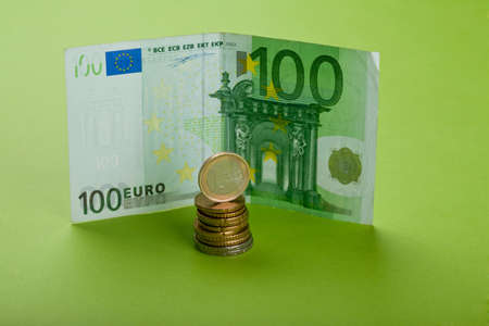 One hundred Euro bill and coins on the paper
