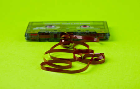unwound: Old  audio cassette with unwound tape on the paper
