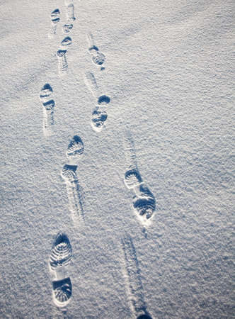 set of footprints in the snow receding into the distance