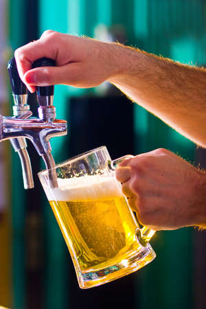 glass being filled with draft beer by barman